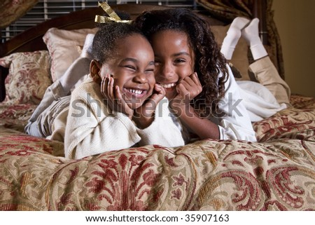 Two little sisters with happy smiles - stock photo