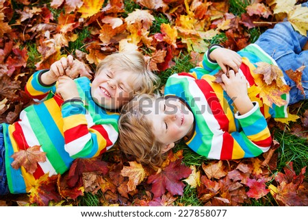 Two little smiling kid boys lying in autumn leaves in colorful clothing. Happy siblings having fun in autumn park on warm day. - stock photo