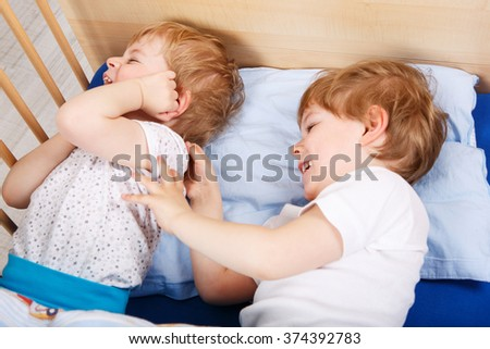 Two little toddler boys having fun and fighting together in bed before sleeping, indoors. Kid boys, little twins in love. - stock photo