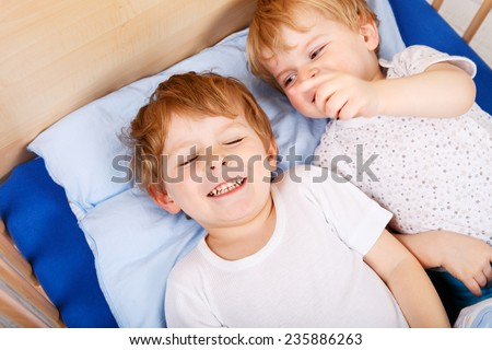 Two little toddler boys having fun in bed before sleeping. Sibiling kids playing together. - stock photo