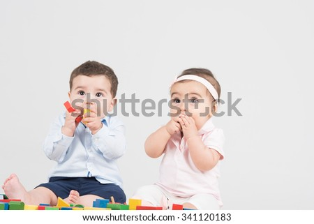 Two little trouble trying to chew on their toys together - stock photo