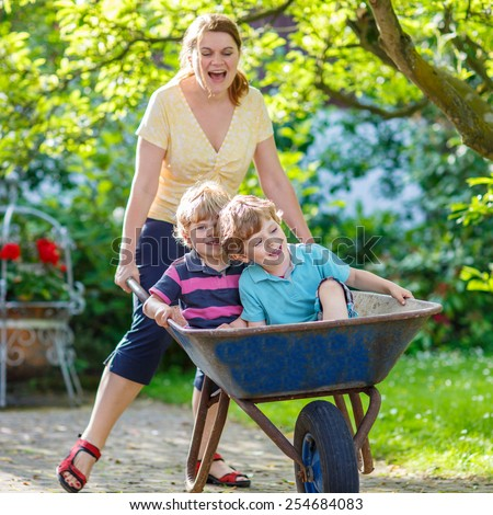 Two little twins having fun in a wheelbarrow pushing by mum  in domestic garden, on warm sunny day. Active outdoors games for kids in summer. - stock photo
