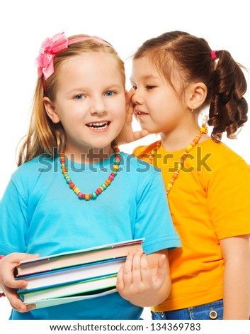 Two little 6-7 years old Asian and Caucasian girls with pile of books gossip, isolated on white - stock photo
