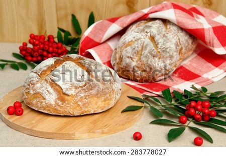 Two loaf of bread on table and rowan, horizontal - stock photo