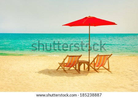 Two lounge chairs and a sunshade umbrella on the beach - stock photo