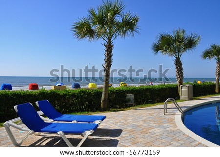 Two lounge chairs pool side with pretty beach scene in background - stock photo