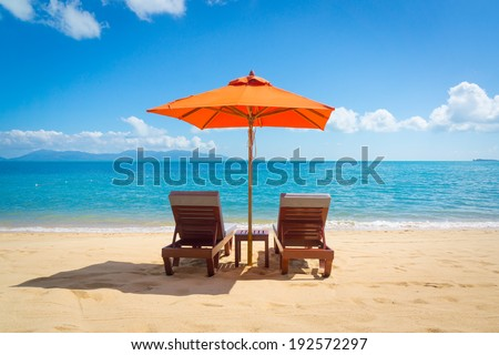 Two lounge chairs with sun umbrella on a beach - stock photo