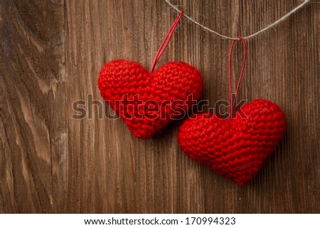 Two love heart hanging on wooden texture background, valentines day card concept - stock photo