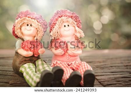 Two Lovely doll sitting on a wooden and bokeh background  in a vintage retro style, with the sunrise, for the day of love, Valentine's Day. - stock photo