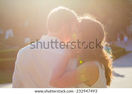 Two lovers in a park - she is whispering something in his ear and he is listening - stock photo
