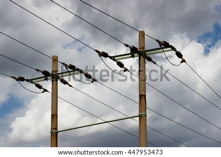 Two low voltage pillars (electricity post) against blue sky with white clouds. - stock photo