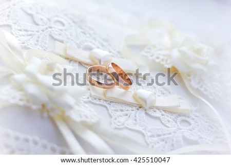 Two luxury golden rings of newlyweds on the lace pillow. Happy wedding day and new family concept. - stock photo