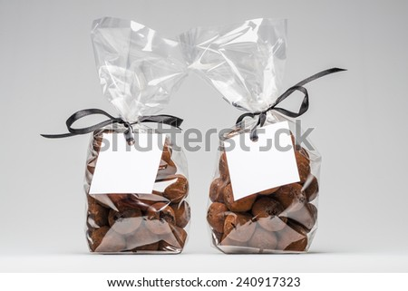 Two luxury plastic bags with elegant black ribbons of chocolate truffles for Christmas gift. Blank label and copy space. Shooting on white background in studio. - stock photo