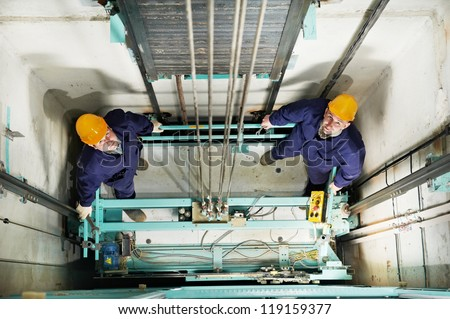 two machinist worker technicians at work adjusting lift with spanners in elevator hoist way - stock photo