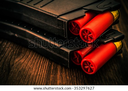Two magazines with red cartridges 12 gauge lies on each other on the wooden table. Close up view, image vignetting and the orange-blue toning - stock photo