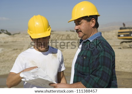 Two male architects wearing hard hat at construction site - stock photo