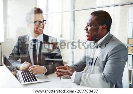 Two male colleagues discussing data at meeting - stock photo