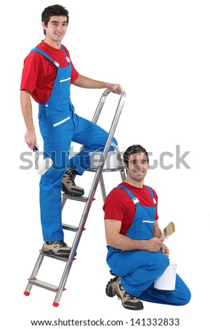 Two male decorators wearing the same outfit - stock photo