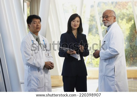 Two male doctors talking to Asian businesswoman - stock photo