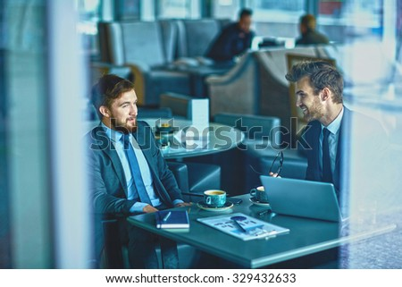 Two male employees consulting in cafe - stock photo