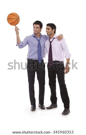 Two male executives with a basketball - stock photo