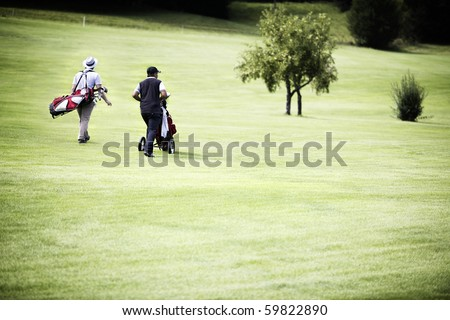 Two male golf player walking on fairway with their golf bags, plenty of copy-space. - stock photo