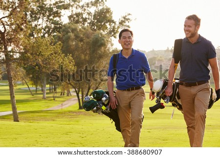 Two Male Golfers Walking Along Fairway Carrying Bags - stock photo
