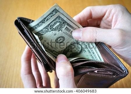 Two male hands holding a leather wallet with US Dollars cash inside  - stock photo