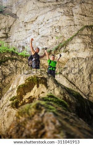 Two male hikers with arms raised standing on a huge cliff at the entrance of a cave - stock photo