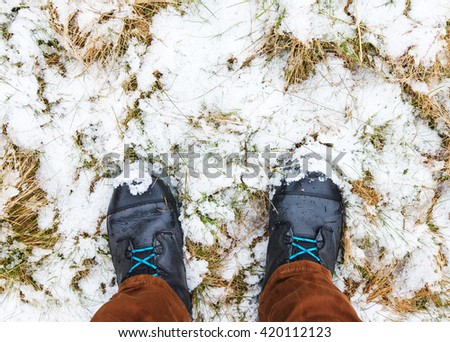 Two male legs with hiking boots standing on snowy grass - stock photo