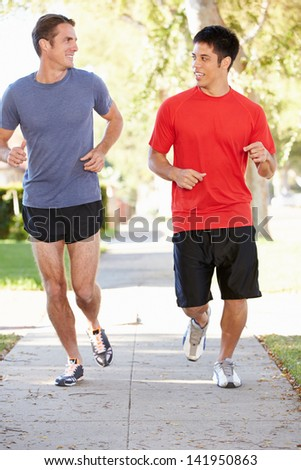 Two Male Runners Exercising On Suburban Street - stock photo