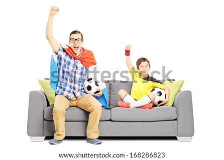 Two male sport fans seated on a sofa watching sport isolated on white background - stock photo