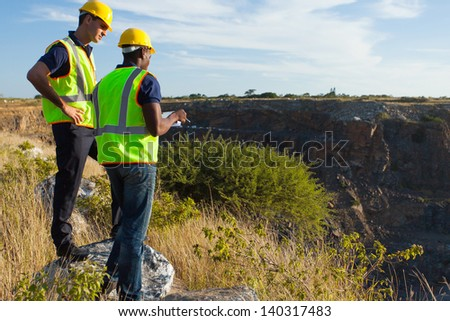 two male surveyors working at mining site - stock photo