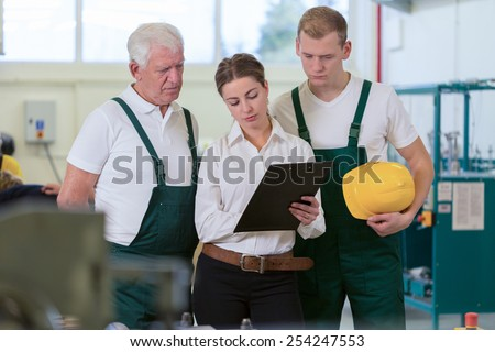 Two male warehouse workers and young female supervisor - stock photo