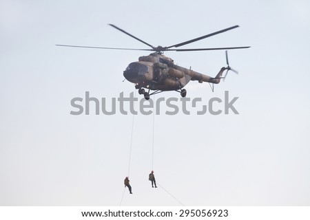 Two man climb from helicopter down a rope - stock photo