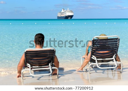 Two man in chairs resting on the beach and watching cruise ship - stock photo