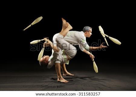 Two man juggling clubs isolated black background  - stock photo