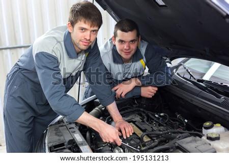 Two man mechanics looking a diagnostics equipment, servicing car - stock photo