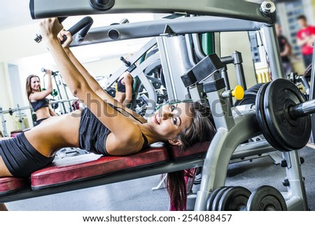 two man three woman with long blond brunette hair sitting smiling face Portrait of three young adult Girls do exercise for legs and hands. in fitness gym on mirror with reflection and window background - stock photo