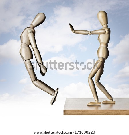 Two manikins, one pushing the other off an edge  - stock photo