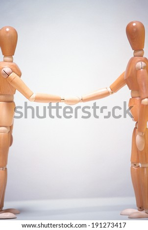 Two mannequins shaking hands - stock photo