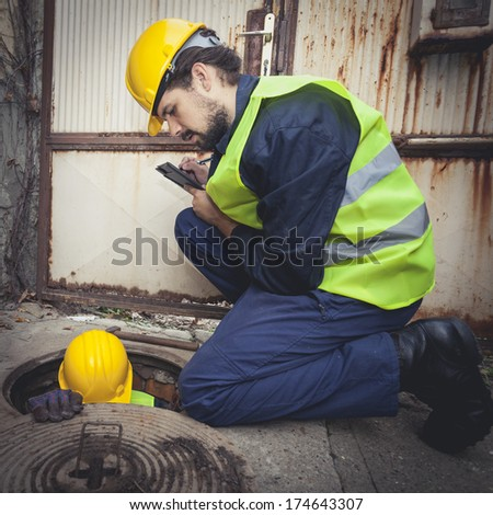 Two manual hard workers on field writing down the water inside of manhole at the road. Detail, view from above. - stock photo