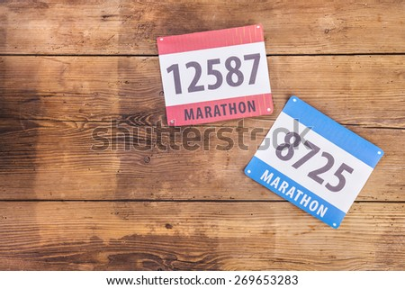 Two marathon race number laid on a wooden floor background - stock photo
