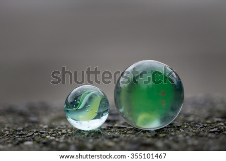 Two marbles on the sidewalk in close up. - stock photo