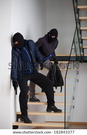 Two masked and armed criminals standing on the stairs - stock photo