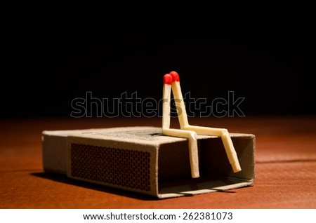 Two match humans sitting on a matchbox on a dark background - stock photo