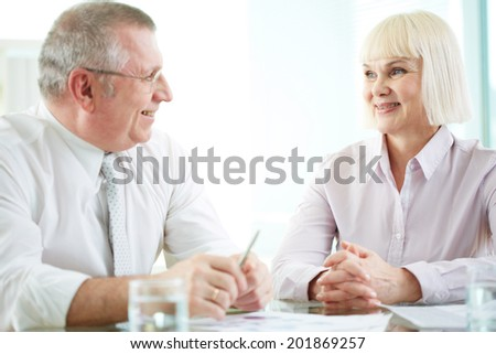 Two mature business partners discussing ideas or plans at meeting - stock photo