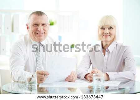 Two mature business partners looking at camera with smiles - stock photo