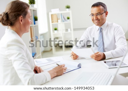 Two mature business partners looking at one another while speaking in office - stock photo