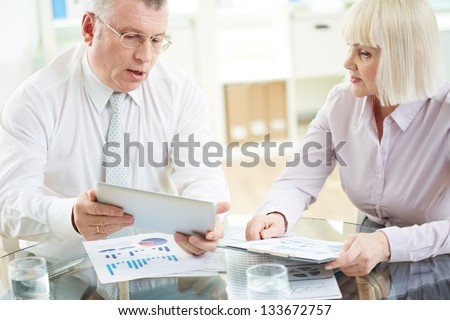 Two mature business partners working with paper and electronic documents at meeting - stock photo